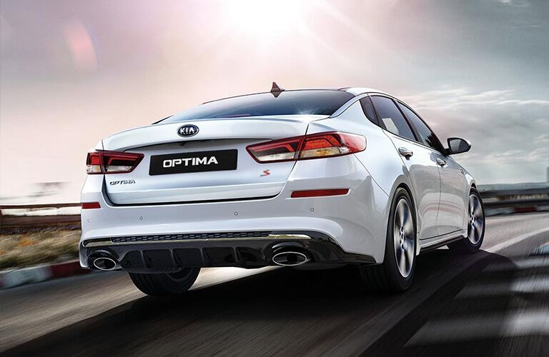 Exterior view of the rear of a silver 2019 Kia Optima driving on an empty road