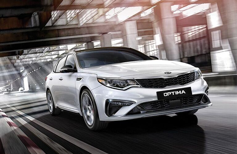 Exterior view of the front of a silver 2019 Kia Optima driving down a city street