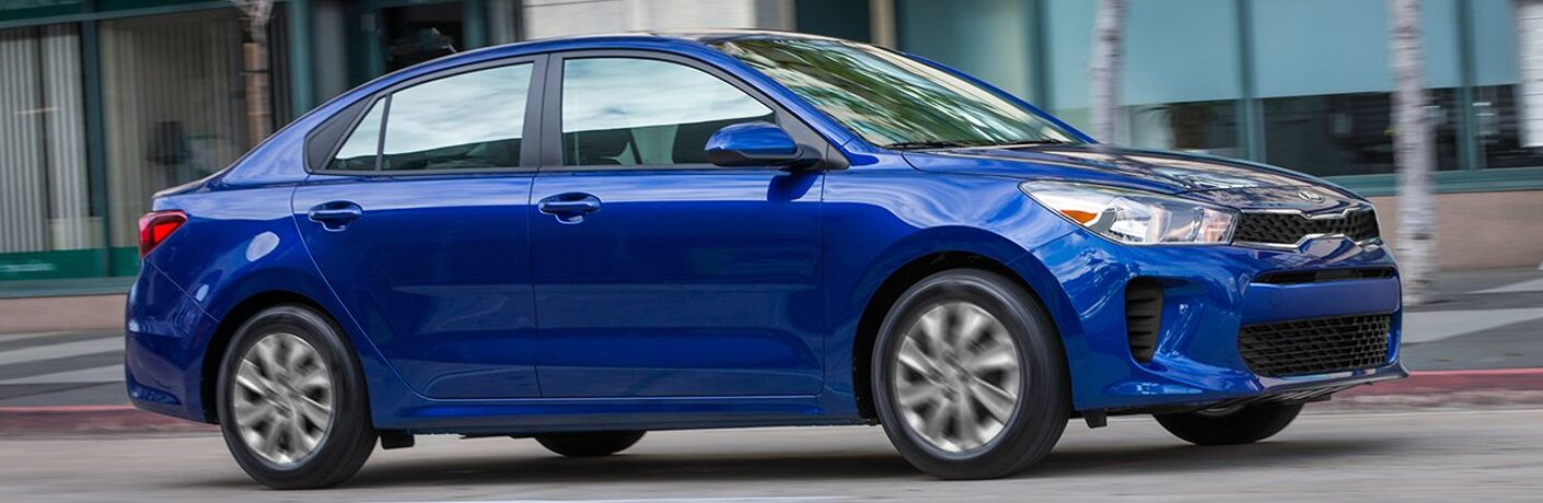 Exterior view of a blue 2019 Kia Rio driving down a city street
