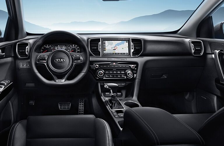 Interior view of the black steering wheel and touchscreen inside of a 2019 Kia Sportage