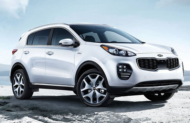 Exterior view of a silver 2019 Kia Sportage parked in the sand at a beach