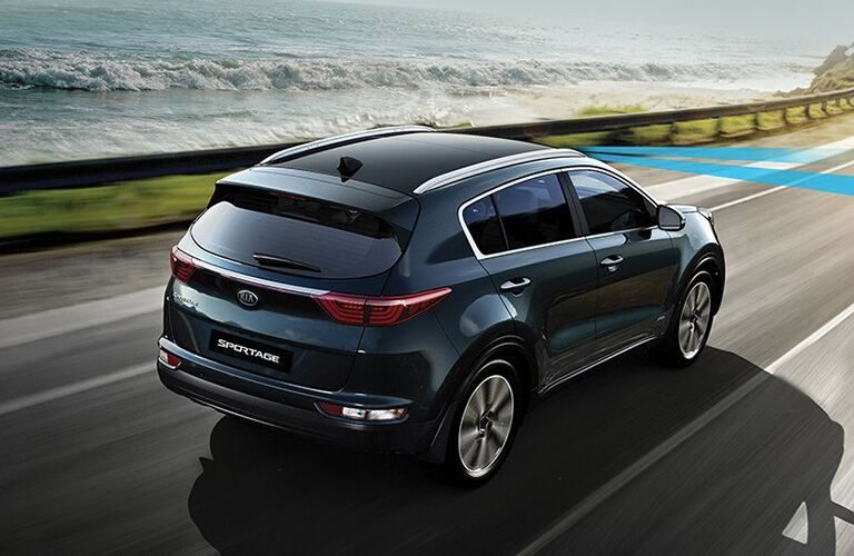 Exterior view of the rear of a dark blue 2019 Kia Sportage driving down a two-lane highway