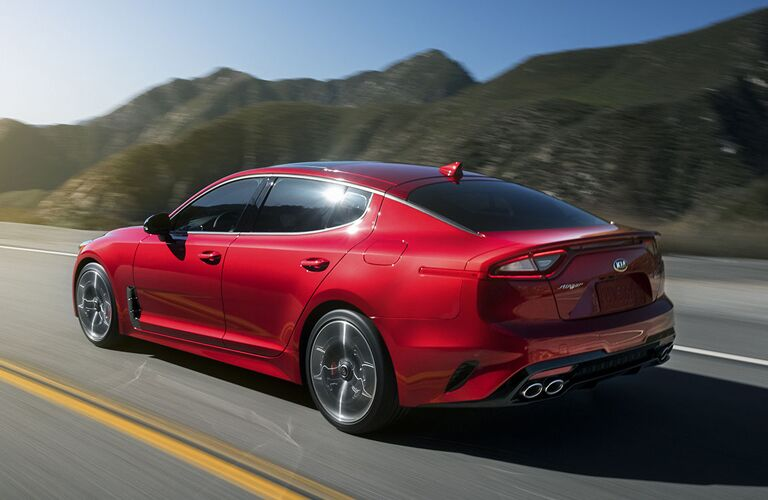 Exterior view of a red 2019 Kia Stinger driving down a highway surrounded by mountains