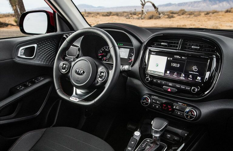 Interior view of the black steering wheel and touchscreen inside a 2020 Kia Soul