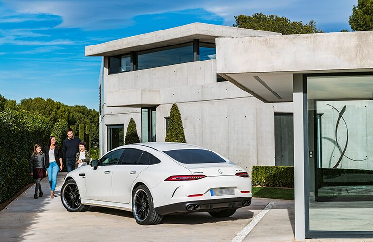 Family walking towards white 2019 Mercedes-AMG® GT Coupe