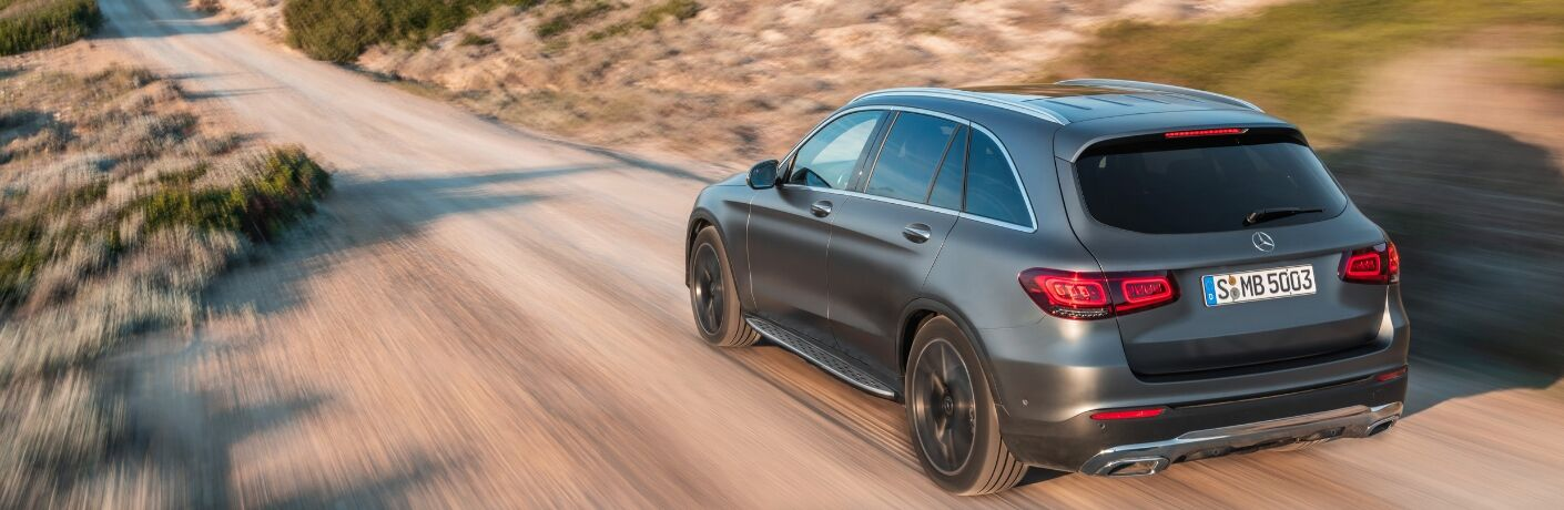 Grey 2020 Mercedes-Benz GLC SUV driving down dirt road