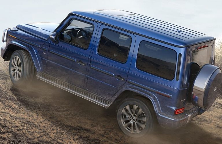 Blue 2020 Mercedes-Benz G-Class driving up hill off of the road from exterior drivers side