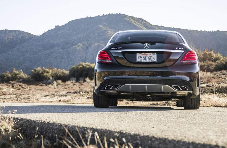 rear view of a black 2018 Mercedes-Benz C-Class parked in front of mountains