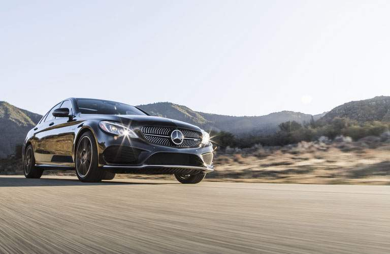 side view of the 2018 Mercedes-Benz C-Class driving in front of mountains