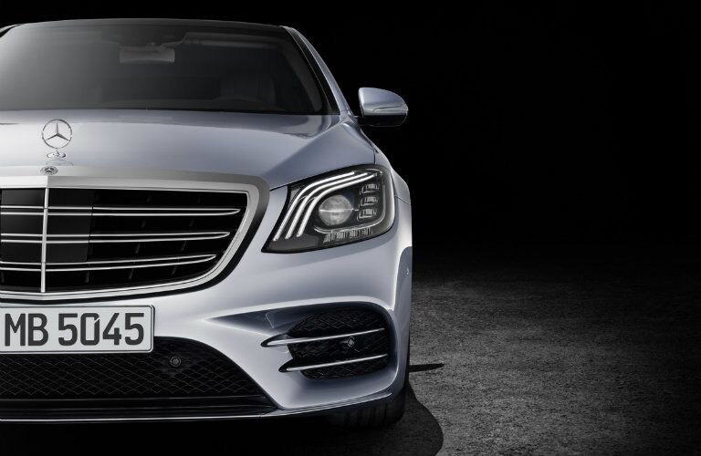 close up shot of a silver Mercedes-Benz S-Class sitting in a dark showroom