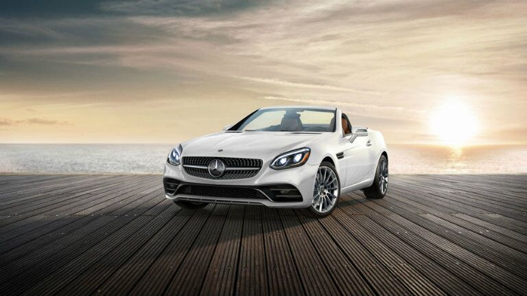 White Mercedes-Benz SLC Roadster sitting on the boardwalk with a sunset