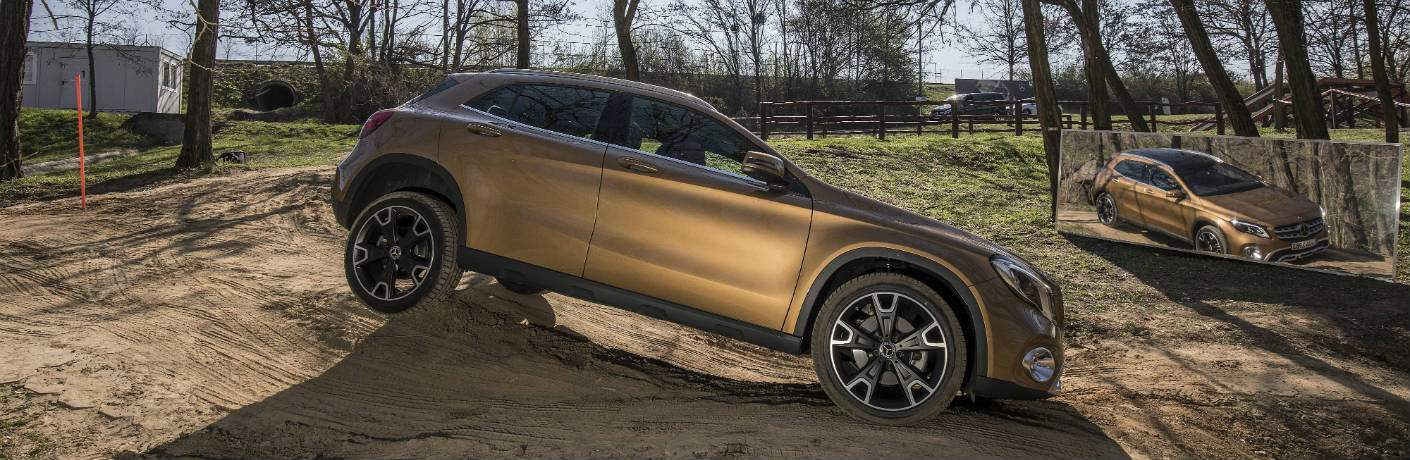 gold 2018 Mercedes-Benz GLA on a rough terrain obstacle course