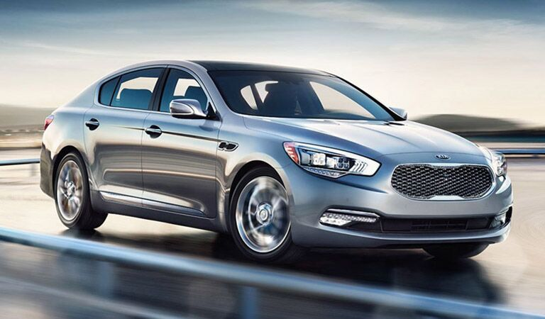 Kia K900 Driving Down Road Side and Front End View in Silver
