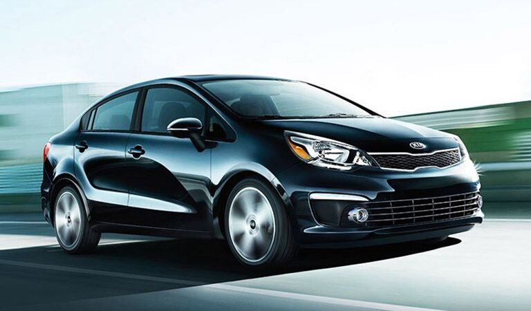 Kia Rio in Navy Driving Down Road