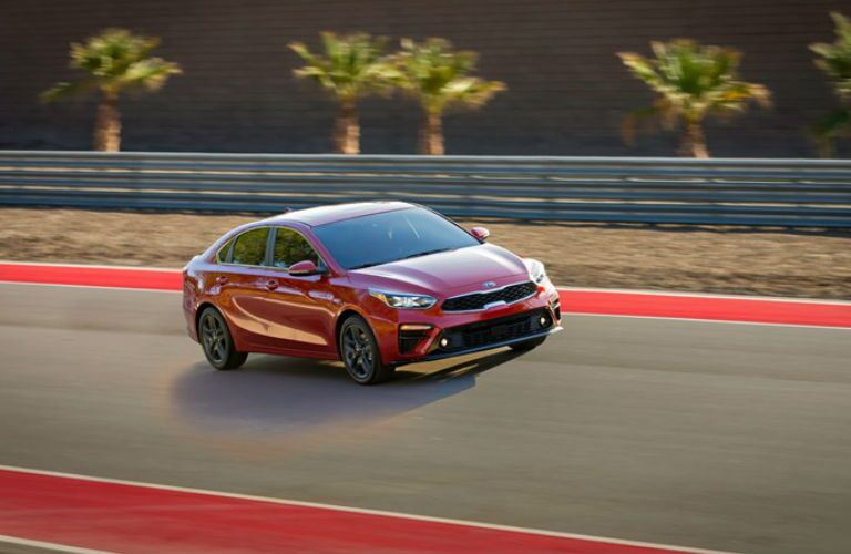2019 Kia Forte Driving Down Road in Red Coloring