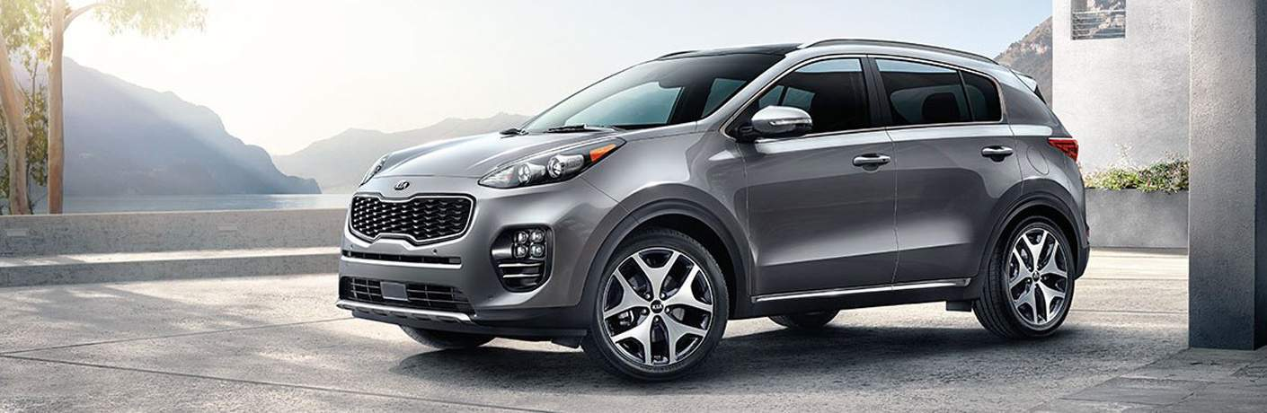 side view of a grey 2018 Kia Sportage with misty mountains in the background