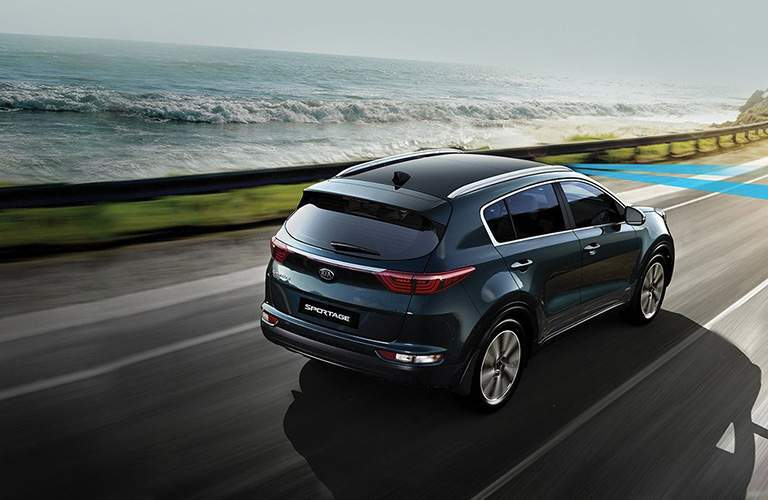 rear view of the 2018 Kia Sportage driving by the ocean with driver assistance on