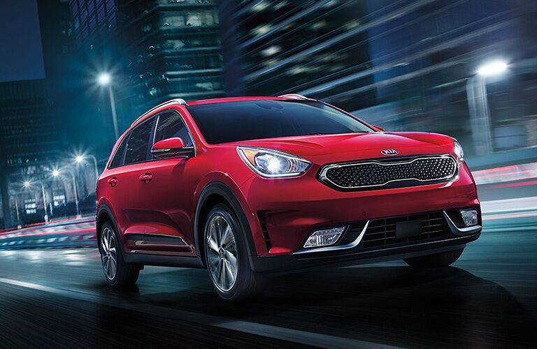 A red 2019 Kia Niro drives down a road in a city.