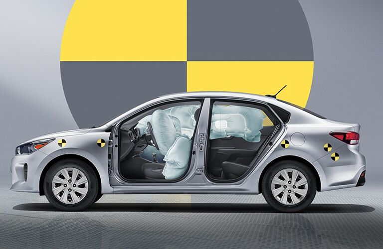 2019 Kia Rio exterior side view showcasing activated airbags with a large crash test icon in the background.