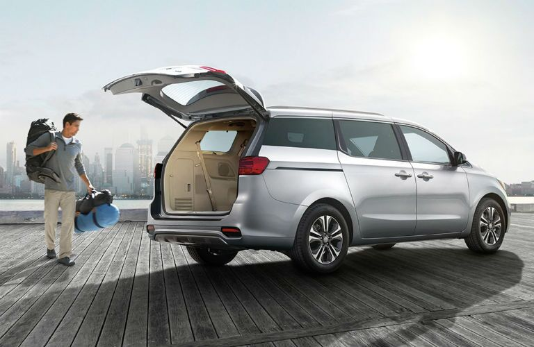 Man loading luggage into the cargo area of the 2019 Kia Sedona