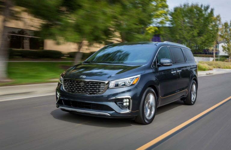 A front left quarter photo of the 2021 Kia Sedona on the road.
