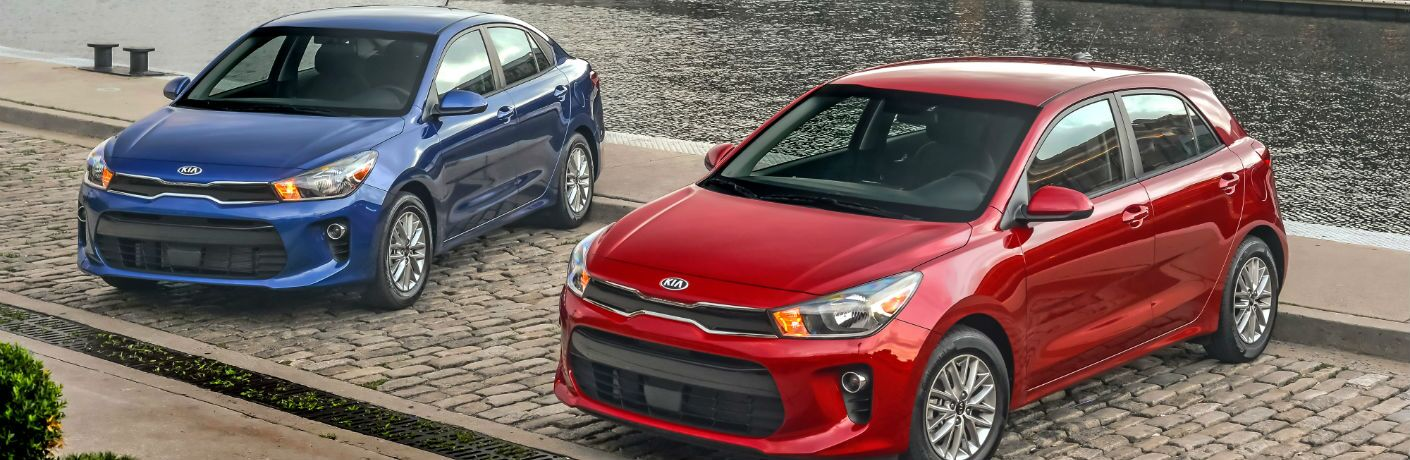 A photo of the sedan and hatchback versions of the 2020 Kia Rio parked by a river.