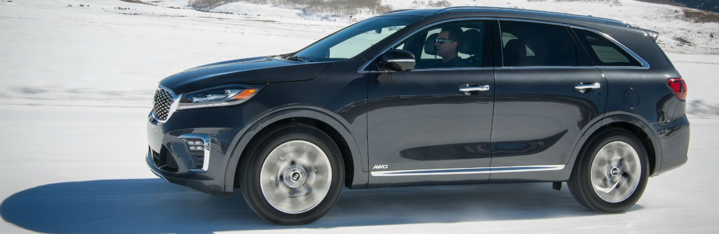 A left profile photo of the 2020 Kia Sorento driving on the snow.