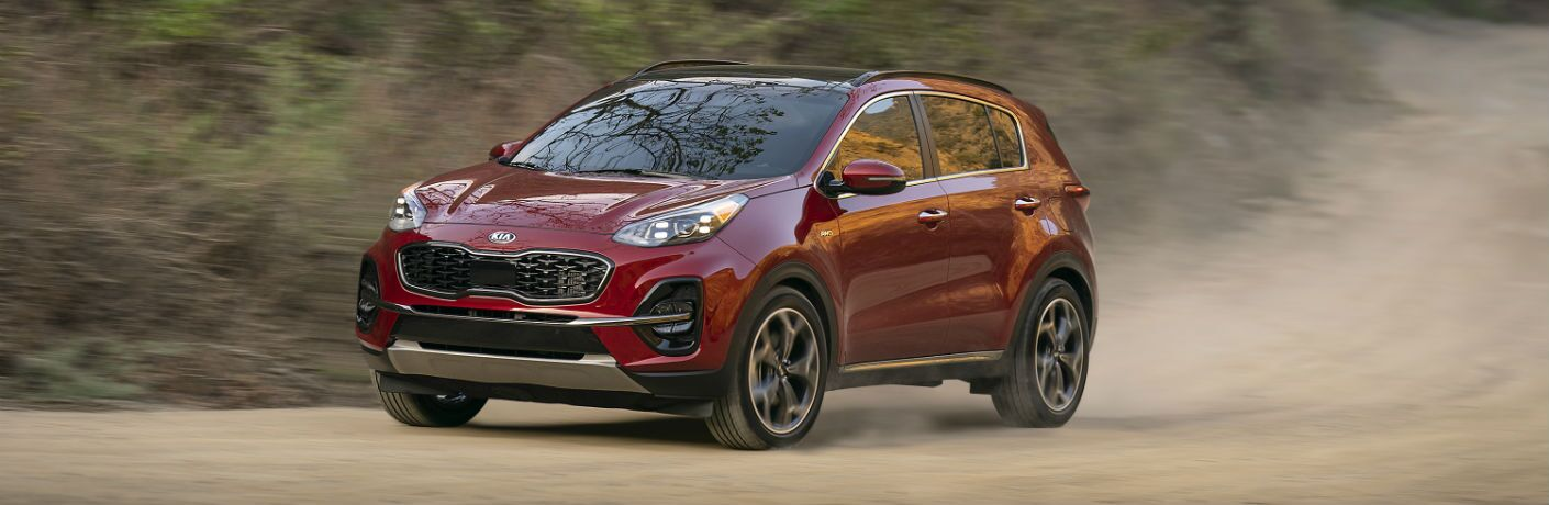 A front left quarter photo of the 2021 Kia Sportage on a dusty road.