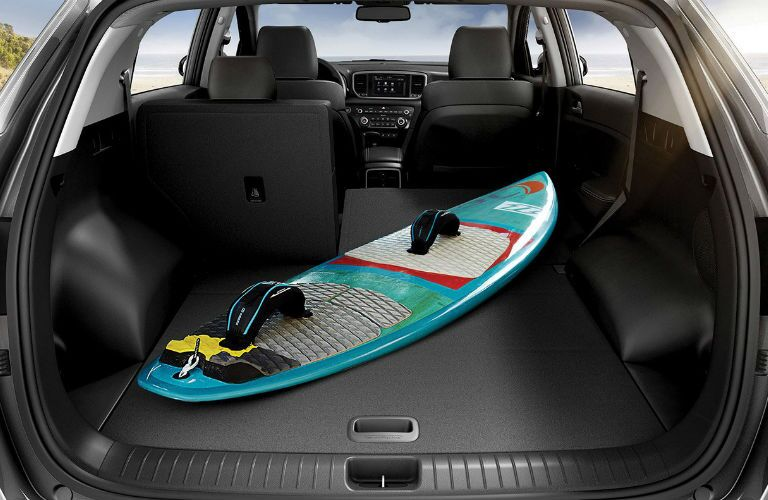 A photo of a surf board in the back of the 2020 Kia Sportage.