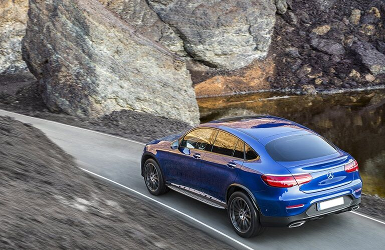 Blue 2017 Mercedes-Benz GLC driving between big rocks