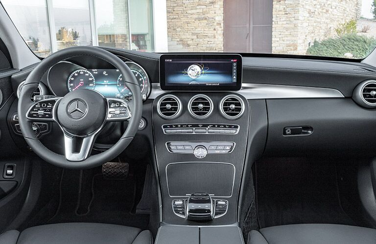 Front interior of the 2019 Mercedes-Benz C-Class luxury sedan showing the steering wheel and dashboard