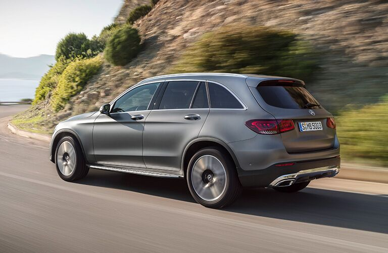 2020 MB GLC SUV exterior back fascia and drivers side going fast on road with blurred grassy hill on right