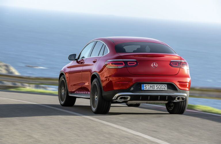 2020 MB GLC Coupe exterior back fascia and drivers side on blurred road overlooking hazy ocean
