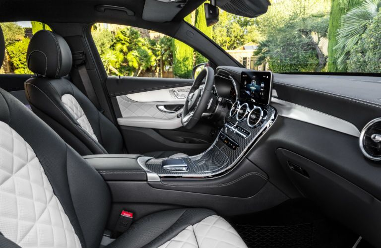 2020 MB GLC Coupe interior side view of seats dashboard touchscreen and steering wheel with trees