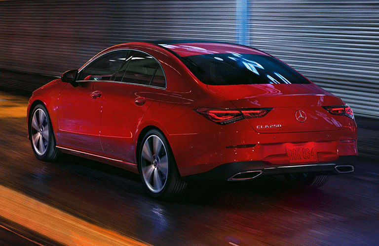 2021 Mercedes-Benz CLA Coupe exterior rear shot with red paint color driving through a city at night