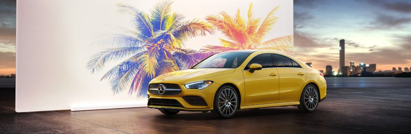 2021 Mercedes-Benz CLA Coupe exterior shot with yellow paint color parked next to a white billboard with neon palm trees