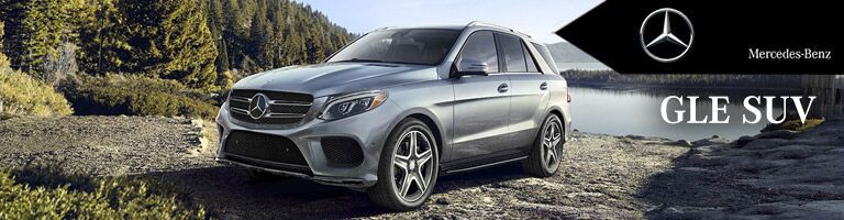 silver Mercedes-Benz GLE SUV parked by a lake