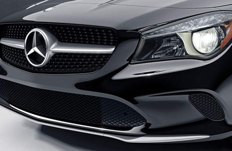 Close up of front grille, headlights, and Mercedes-Benz badging on the 2018 Mercedes-Benz CLA