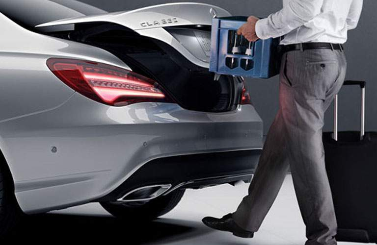 Man opening the trunk of the 2018 Mercedes-Benz CLA using his foot while holding a crate