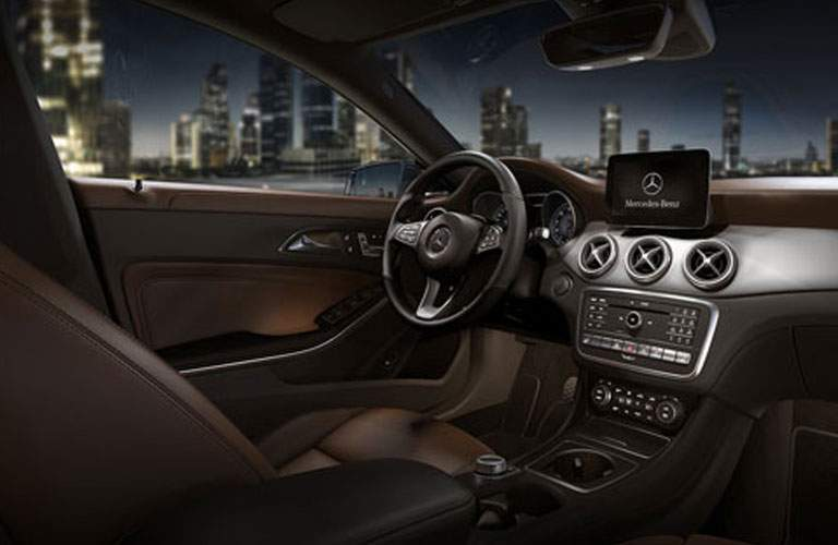 Interior view of the 2018 Mercedes-Benz CLA with focus on the center console and steering wheel