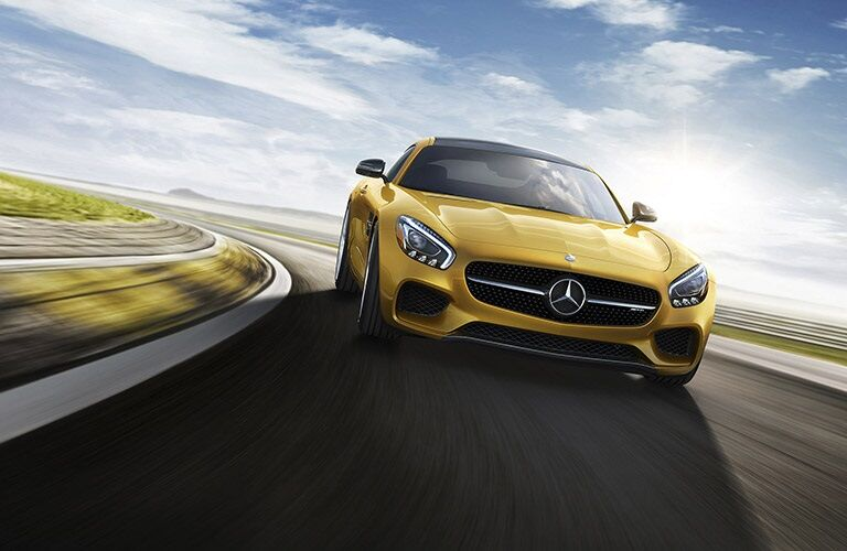 yellow 2017 Mercedes-Benz AMG® GT taking a left turn on track