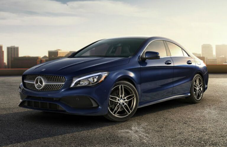 blue 2018 Mercedes-Benz CLA parked in front of city skyline