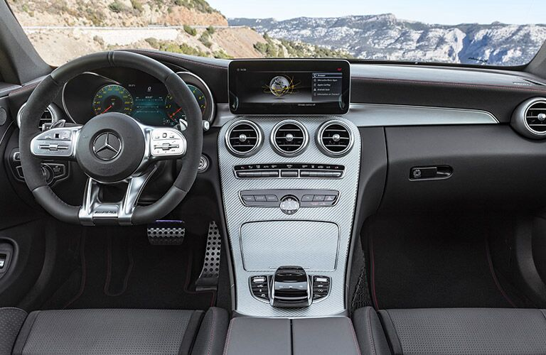 Interior of a 2019 Mercedes-Benz C-Class with a view of the dashboard and through the windshield, with rocky mountains spread out in the distance.