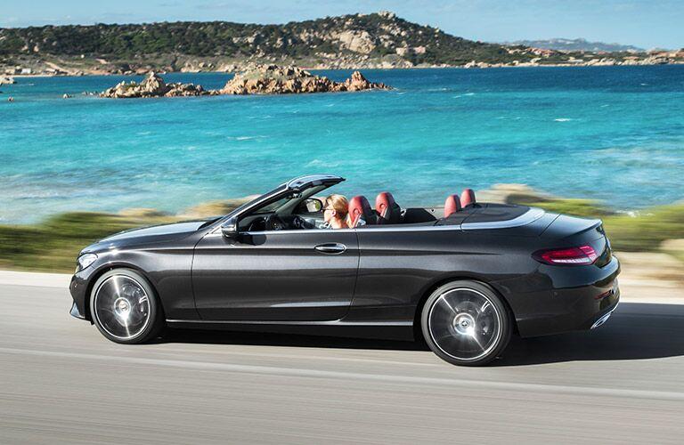 Woman drives a black 2019 Mercedes-Benz C-Class Cabriolet along a sunny, rocky seaside.
