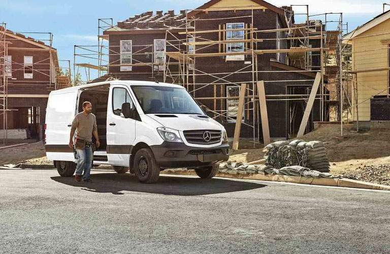 Construction worker getting out of Mercedes-Benz Sprinter van into workplace yard
