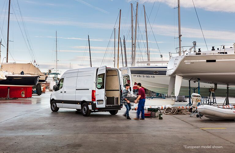 2018 Mercedes-Benz Sprinter van exterior shot parked by a shipping dock with boats and water as men load the trunk
