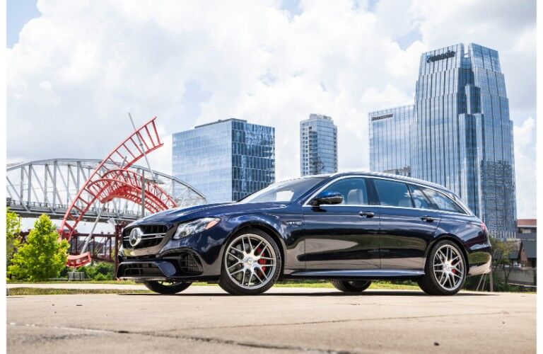 2018 Mercedes-AMG E 63 S Wagon exterior shot dark blue paint job parked outside by a bridge and skyscrapers