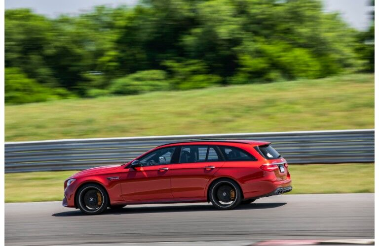 2018 Mercedes-AMG E 63 S Wagon exterior side shot red paint job driving through the country with a blurry background