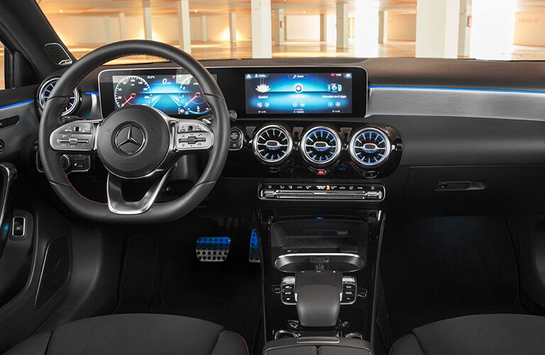 2019 Mercedes-Benz A-Class Sedan interior shot of driver's view of steering wheel, dashboard display, transmission, and pedals