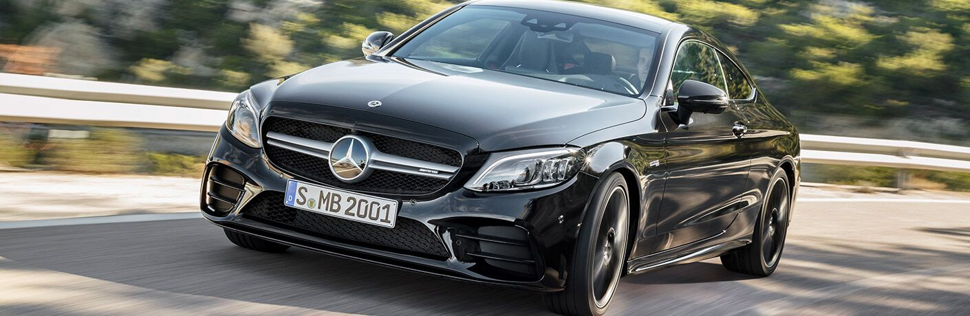 2019 Mercedes-Benz C-Class Coupe exterior close up of black paint color as it drives along the railing of a forest highway